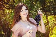 有葡萄酒杯和葡萄的妇女 库存照片