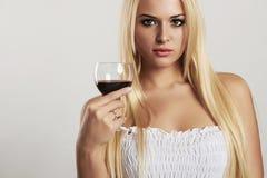 有葡萄酒杯的美丽的白肤金发的女孩 干红葡萄酒 有酒精的性感的少妇 免版税图库摄影