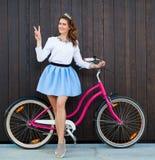 有葡萄酒桃红色自行车的时髦时兴的女孩在黑木背景 展示标志胜利 被定调子的照片 现代青年生活方式 免版税库存图片