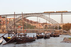 有葡萄酒桶的传统小船与地铁在Dom雷斯桥梁和波尔图市训练在背景中 库存照片