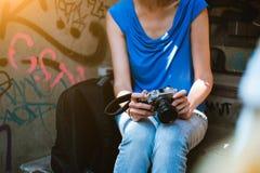 有葡萄酒照相机的少妇在手中坐台阶 库存照片