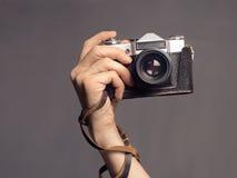 有葡萄酒照相机的手 免版税库存图片