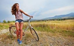 有葡萄酒自行车的妇女在乡下公路 库存照片
