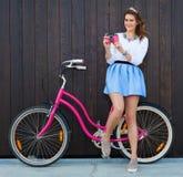 有葡萄酒自行车的时髦时兴的女孩在木背景 桃红色葡萄酒照相机在她的手上 被定调子的照片 现代青年时期Lifesty 库存照片