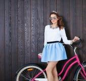 有葡萄酒自行车的时髦时兴的女孩在木背景 被定调子的照片 现代青年生活方式概念 关闭 免版税库存照片