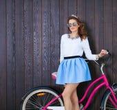 有葡萄酒自行车的时髦时兴的女孩在木背景 被定调子的照片 现代青年生活方式概念 关闭 免版税库存图片
