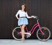 有葡萄酒自行车的时髦时兴的女孩在木背景 被定调子的照片 现代青年生活方式概念 免版税库存照片