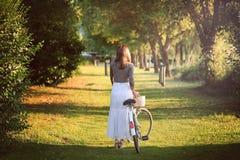 有葡萄酒自行车的浪漫妇女 免版税库存照片
