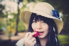 有葡萄酒衣物的一个逗人喜爱的亚裔泰国女孩咬住strawber 库存照片