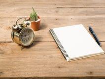 有葡萄酒闹钟和黑笔的空白的在木桌上的笔记本和仙人掌 免版税库存图片