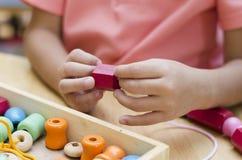有蒙台梭利材料色的小珠的小男孩 免版税库存照片