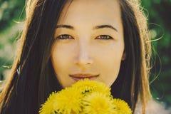 有蒲公英花束的美丽的少妇  免版税库存图片