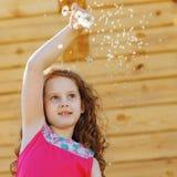 有蒲公英花的逗人喜爱的小女孩在春天公园 免版税库存照片