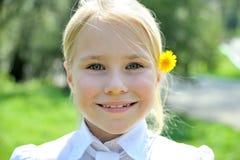 有蒲公英画象的小微笑的女孩 免版税库存图片