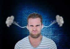 有蒸汽的愤怒年轻人在耳朵 背景黑色蓝色 免版税库存照片