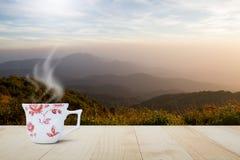 有蒸汽的热的咖啡杯在被弄脏的草甸的葡萄酒木台式和在日出期间的有雾的山背景 图库摄影