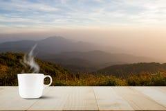 有蒸汽的热的咖啡杯在被弄脏的草甸的葡萄酒木台式和在日出期间的有雾的山背景 免版税图库摄影