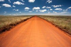 有蓝天和远的天际的农村橙色土路 免版税库存图片