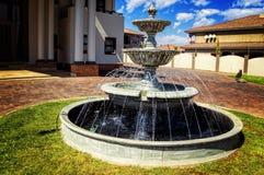 有蓝天和绿草的现代议院与喷泉 免版税库存图片