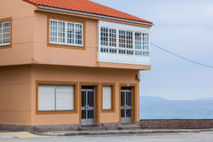 有蓝天的橙色海滨别墅在海洋附近 库存照片