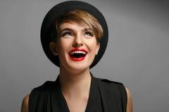 有蓝眼睛和红色嘴唇的美丽的妇女是非常愉快摆在照相机 免版税库存图片