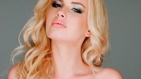 有蓝眼睛和诱人的神色的性感的白肤金发的妇女 股票视频