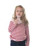 有蓝眼睛和金发的逗人喜爱的甜小女孩举行瓶水喝的7岁 库存图片