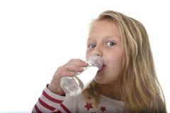 有蓝眼睛和金发的逗人喜爱的甜小女孩举行瓶水喝的7岁 免版税库存照片