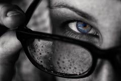 有蓝眼睛的一个女孩看在她的玻璃 图库摄影