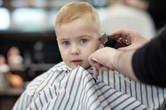 有蓝眼睛的严肃和一点害怕的逗人喜爱的白肤金发的男婴在理发店有洗涤的头由美发师 免版税库存图片