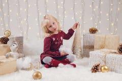 有蓝眼睛的儿童女孩坐与玩具的地板庆祝圣诞节或新年假日的 库存图片