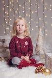 有蓝眼睛的儿童女孩坐与玩具的地板庆祝圣诞节或新年假日的 库存照片