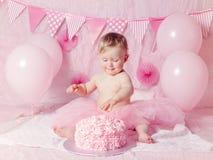 有蓝眼睛的在桃红色芭蕾舞短裙裙子庆祝她的与食家蛋糕的逗人喜爱的可爱的白种人女婴画象第一个生日 免版税库存图片