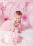 有蓝眼睛的在桃红色芭蕾舞短裙裙子庆祝她的与食家蛋糕的逗人喜爱的可爱的白种人女婴画象第一个生日 免版税图库摄影