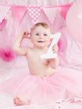 有蓝眼睛的在桃红色芭蕾舞短裙裙子庆祝她的与食家蛋糕的逗人喜爱的可爱的白种人女婴画象第一个生日 图库摄影