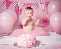 有蓝眼睛的在桃红色芭蕾舞短裙裙子庆祝她的第一个生日的逗人喜爱的可爱的白种人女婴画象  免版税库存图片