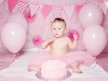 有蓝眼睛的在桃红色芭蕾舞短裙裙子庆祝她的第一个生日的逗人喜爱的可爱的白种人女婴画象  免版税库存照片