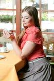 有蓝眼睛的女孩在红色在r的女衬衫饮用的咖啡穿戴了 库存图片