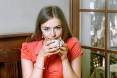 有蓝眼睛的女孩在红色女衬衫饮用的咖啡穿戴了 免版税库存照片
