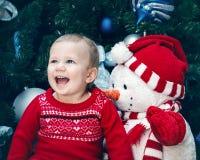 有蓝眼睛的女婴小孩在坐由新年树的红色礼服在雪人玩具附近 库存图片