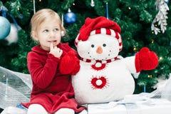 有蓝眼睛的女婴小孩在坐由新年树的红色礼服在雪人玩具附近 图库摄影