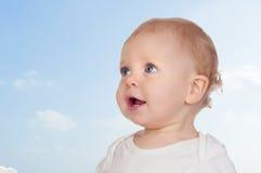 有蓝眼睛的好婴孩与美丽的天空 库存图片
