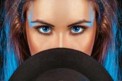 有蓝眼睛的妇女在帽子后 免版税库存照片