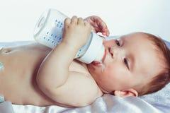 有蓝眼睛的宝贝拿着一个瓶 免版税库存照片