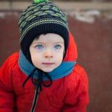 有蓝眼睛的小男孩在冬天步行 免版税库存图片