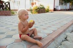 有蓝眼睛的小逗人喜爱的男孩吃玉米的 免版税库存图片