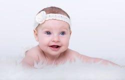 有蓝眼睛的愉快的微笑的女婴 免版税库存照片