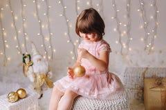 有蓝眼睛的白种人儿童女孩坐与玩具庆祝圣诞节或新年假日的 免版税库存图片