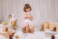 有蓝眼睛的白种人儿童女孩坐与玩具庆祝圣诞节或新年假日的 库存照片