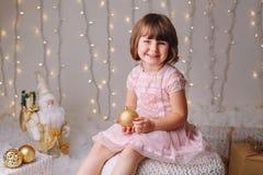 有蓝眼睛的白种人儿童女孩坐与玩具庆祝圣诞节或新年假日的 免版税图库摄影